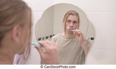 Young attractive millennial man with long hair holds morning oral hygiene. To brush teeth with a mirror in the bathroom. The concept of caries prevention.