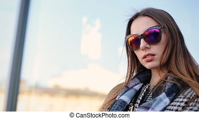 Young attractive model in funny sunglasses professionally posing on camera.