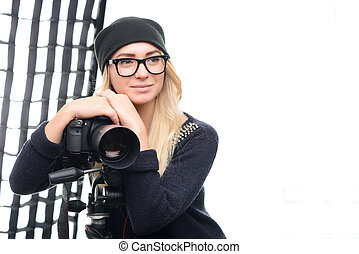 Young attractive model rests against camera onto tripod