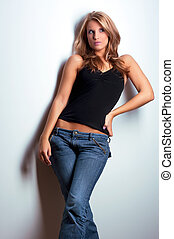 Young attractive model standing near wall