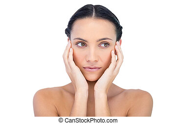 Young attractive model with hands on face looking away