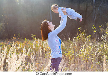 Young attractive mother playing with her baby on sunset