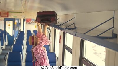 Young attractive mother with daughter going to travel in speed train - puts the suitcase on the top shelf
