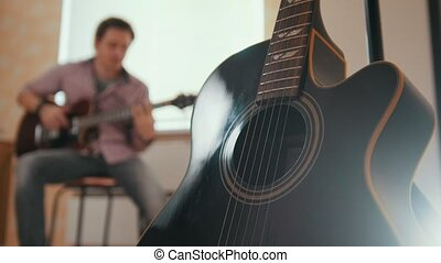 Young attractive musician composes music on the guitar and...