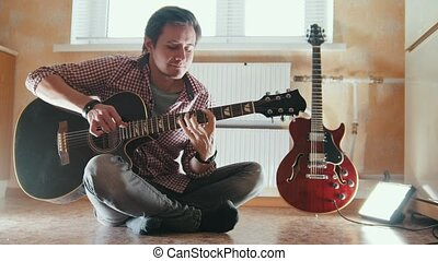 Young attractive musician plays the guitar sitting on the floor in the kitchen