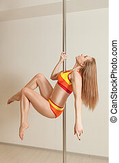 Young attractive pole dance woman in studio