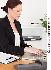 Young attractive red-haired woman in suit typing on her...