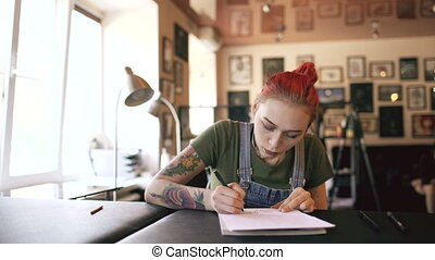 Young attractive red haired woman tattoo artist sitting at table and creating sketch for tattooing in studio indoors