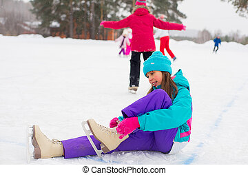young attractive skater girl sitting on the ice