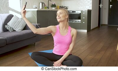 Young attractive sporty woman sitting on yoga mat making...