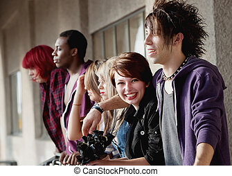 Young attractive teen punk looks towards the camera while her group of friends look away.