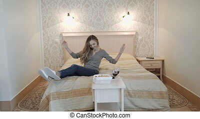Young attractive teenage girl having fun in the bed in a luxury apartment.