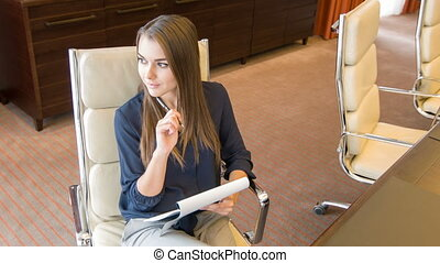 Young attractive thoughtful woman sitting at table in some office