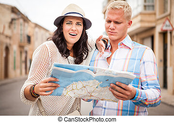 young attractive tourist couple with city map in summer