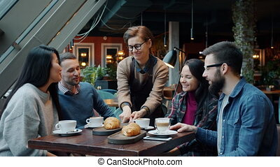 Young attractive waitress in apron is bringing pastry to group of friends sitting at table in cafe having fun talking. Eating out and friendship concept.