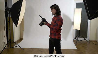 Young attractive white male photographer sitting in his...