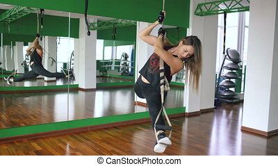 Young attractive woman at the gym working on on trx and training arms with fitness straps in the gym
