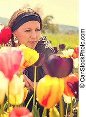 attractive woman behind colorful tulips in the nature