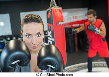 young attractive woman boxer training in a gym