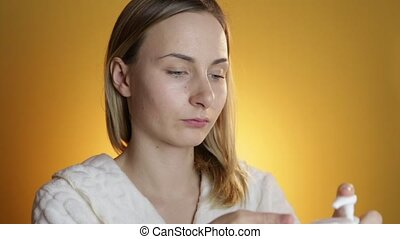 Young attractive woman cleaning her face, on a yellow background