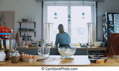 Young attractive woman cooking in the kitchen at home. Beautiful housewife preparing the meal, using kitchen scales.