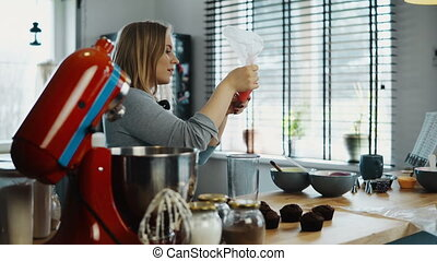 Young attractive woman cooking the cupcakes on her kitchen. Blonde female puts the cream for decoration on pastry bag.