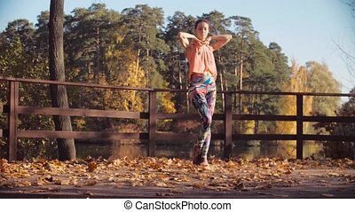 Young attractive woman dancing on the bridge alone