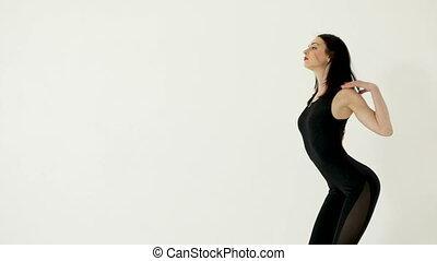 Young attractive woman dancing on white background, side...