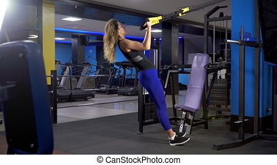 Young attractive woman does core abs crossfit oblique training with fitness straps in the gym's studio. TRX
