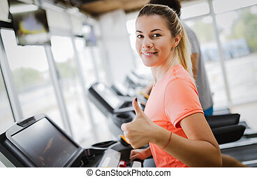 Young attractive woman doing cardio training in gym - Young...