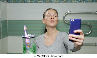Young attractive woman doing selfie phone in the bathroom of the hotel room. She smiles and changes the posture for a better photo