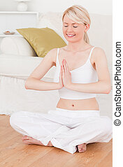 Young attractive woman doing yoga in the living room
