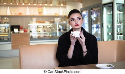 Young attractive woman drinking coffee in cafe, steadicam...