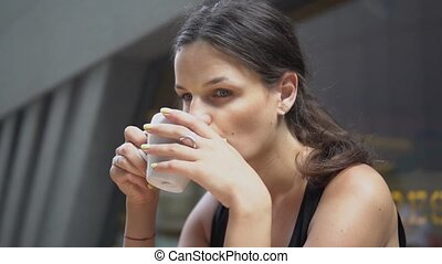 Young attractive woman drinking coffee in cafe.