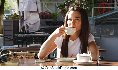 Young, attractive woman drinking coffee on the street.