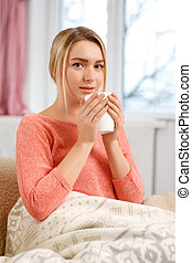 Young attractive woman drinking tea at home.