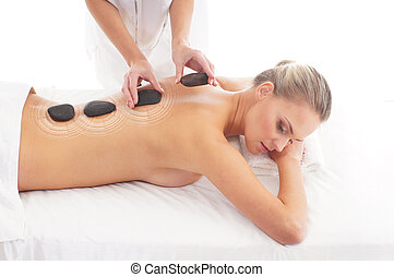 Young attractive woman getting hot stone treatment over...