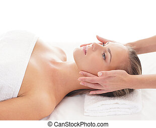 Young attractive woman getting massaging treatment over...