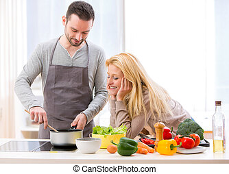 Young attractive woman give food to her husband to taste -...