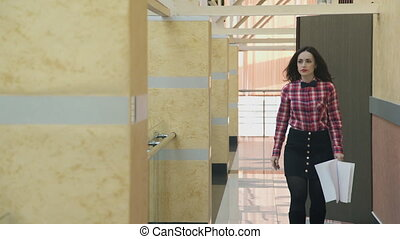 Young attractive woman go along hall with papers in business center.