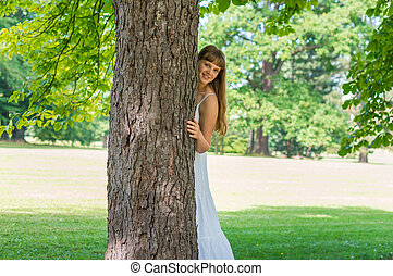 Young attractive woman hiding behind a tree