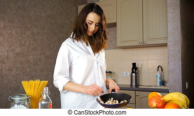 Young attractive woman holding a frying pan in her hand.