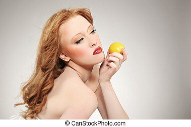 Young attractive woman holding a lemon