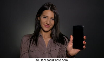 Young attractive woman holding smart phone in hand and pointing at it