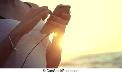 Young attractive woman holding smartphone at the beach