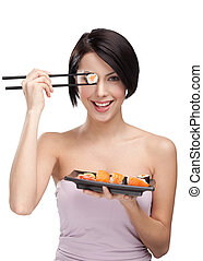 Young attractive woman holding sushi roll with a chopsticks