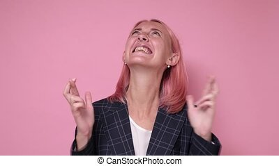 Young attractive woman holds her fingers crossed and eyes closed, wishful thinking, studio shoot isolated on pink background
