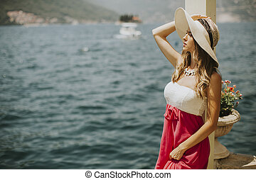 Young attractive woman in a dress relaxing by the sea