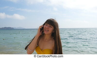Young attractive woman in a swimsuit is talking on mobile phone on a sea beach. Happy girl in bikini speaking on the cellphone on the background of the ocean. Call from the summer vacation. Close up