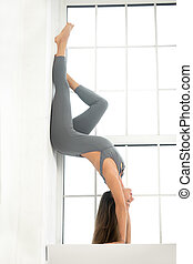 Young attractive woman in Adho Mukha Vrksasana pose, window...